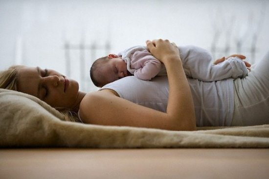 Новорожденный спит на животе у матери