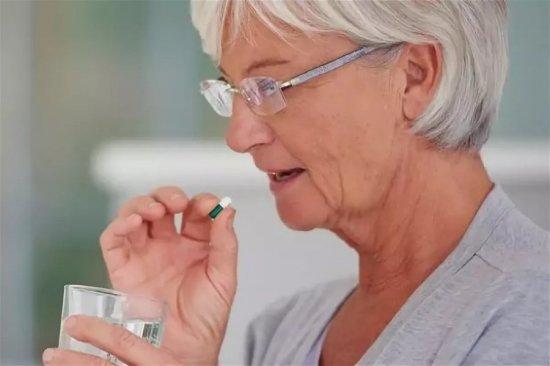 Пожилая женщина принимает лекарство