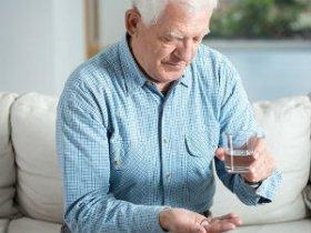 Пожилой человек принимает лекарство